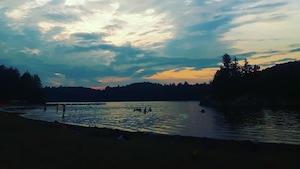 La plage du lac Stukely a été fermée temporairement après des tests effectués le 3 juillet. Des baigneurs se baignent au coucher du soleil.