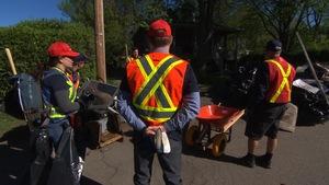 Des bénévoles se préparent à nettoyer les rues sinistrées de Laval avec des sacs et des brouettes.