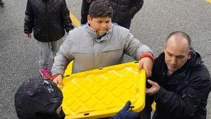 Des élèves soulèvent des caisses de denrées
