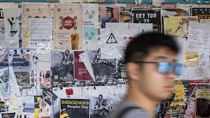 Un étudiant passe devant un mur d'affiches diverses.