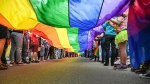 Des personnes tiennent le drapeau arc-en-ciel LGBT.