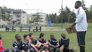 Des jeunes assis dans l'herbe en tenue sportive écoutent leur entraîneur.