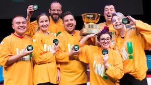 Un groupe de personnes vêtues de chandails jaunes soulèvent un trophée.
