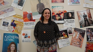 Lisa Bertrand devant un mur d'affiches d'artistes variés.
