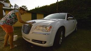 Lise Boucher nettoie avec un chiffon bleu son imposante voiture blanche.