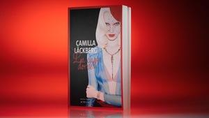 La couverture du livre «La cage dorée» de Camilla Läckberg sur un fond rouge sang.