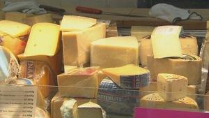 Étalage de fromages diversifiés dans un marché d'alimentation.