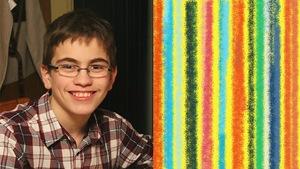 Un garçon avec des lunettes et vêtu d'une chemise à carreaux sourit.