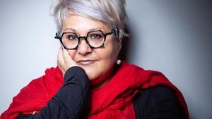 Portrait en couleur de l'autrice Lynda Dion, une main sur la joue droite, foulard rouge autour du cou, lunettes vertes hexagonales, cheveux courts.