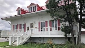 La Maison Price se dresse sous un ciel gris.