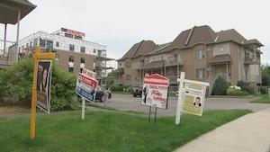 Les pancartes à vendre sont nombreuses devant des condos à Gatineau.