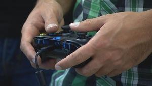 Joueur de jeux vidéo tenant une manette.