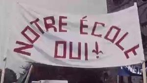 Grande bannière avec l'inscription «Notre école OUI» dans une manifestation