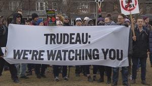 """Un petit groupe de manifestants brandissent une banderole """"Trudeau we're watching you"""""""