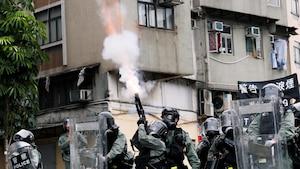 Des policiers avec des boucliers tirent des gaz lacrymogène en l'air