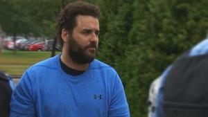 Un homme à la barbe portant un chandail bleu