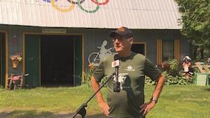 Marcel Jobin au micro de Radio-Canada devant un bâtiment de ferme où il y a des anneaux olympiques sur le toit ainsi qu'un panneau sur le mur extérieur qui dit : le fou en pyjama.