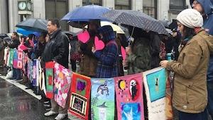 Des dizaines de personnes marchent sous la pluie dans le quartier Downtown Eastside de Vancouver, le 14 février 2016, en hommage aux femmes autochtones disparues ou assassinées.