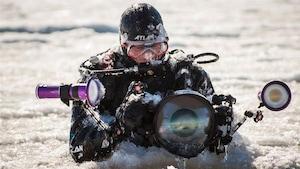 Le photographe sous-marin Mario Cyr, en combinaison de plongée, prend une photo alors qu'il est à la surface d'une étendue d'eau glacée