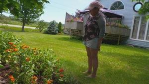 Marthe Laverdière regarde des fleurs dans un jardin