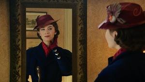 Emily Blunt, jouant Mary Poppins, se regarde dans un miroir, touchant ses cheveux de la main gauche.