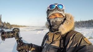 Mathieu Dupuis, photographe dans la neige devant une forêt d'épinettes