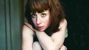 Portrait en couleur de la jeune femme, assise sur une chaise, genoux relevés et pliés, et bras croisés. Elle porte une camisole noire, une jupe en denim et des bas résille.