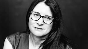 Portrait en noir et blanc de l'auteure Maude Poissant. Elle porte des lunettes et des cheveux longs.