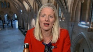 Une femme blonde habillée en rouge s'exprime face caméra.