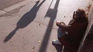 Une personne mendie dans une rue