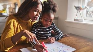 Une mère supervise sa fille qui fait ses devoirs.