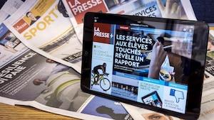 La version numérique de La Presse (La Presse +) sur une tablette en avant-plan et plusieurs cahiers du journal La Presse sous forme papier en arrière-plan