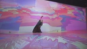 Un danseur seul sur scène entouré de projections psychédéliques.