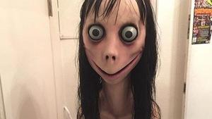 Une photo montrant une sculpture d'une femme aux traits déformés. Ses yeux sont grands et exorbités et sa bouche forme un sourire exagérément large, qui monte presque jusqu'à ses oreilles. Ses cheveux noirs, longs, sont décoiffés et ont l'air gras.