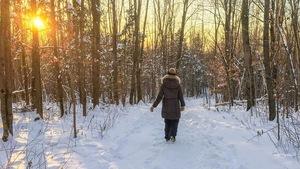 Une promeneuse, de dos, marche sur un sentier enneigé.