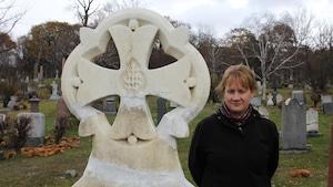 Une importante pierre tombale en forme de croix et à la droite, sur l'image, Myriam Cloutier, une femme d'âge moyen aux yeux mi-clos, sourit, sa frange lui recouvre le front.