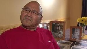 Un homme autochtone du nom de Nicky Obed regarde devant lui alors que sont empilés des souvenirs de son enfance derrière lui.