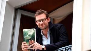 L'écrivain Nicolas Mathieu pose avec son livre à une fenêtre.