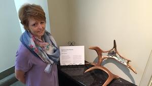 Spirit of the Moose est un panache sculpté, dans lequel on trouve un orignal sculpté. Nicole Frappier pose à côté de l'oeuvre.