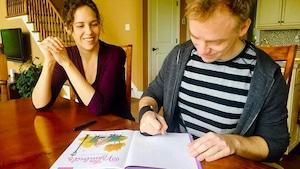 Les deux créateurs de la série les Nombrils, Maryse Dubuc et Marc Delafontaine en train de dessiner une dédicace