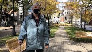 Normand Huard est un homme aux cheveux blancs dans la cinquantaine. Il porte un masque et tient sa valise, en posant pour la caméra.