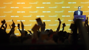 Des mains levées avec un papier et un homme au podium