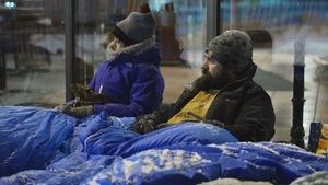 Deux personnes assises dans des sacs de couchage près d'une vitrine en hiver.