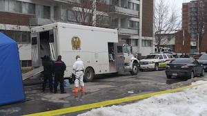 Une voiture des ambulanciers paramédicaux, un camion blanc et une banderole jaune de la police inique que l'opération policière est en cours.