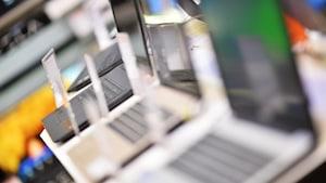 Quatre ordinateurs portables sont présentés dans une boutique de produits électroniques.