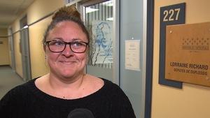 Nancy Lamontagne accorde une devant l'entrée du bureau de la députée de Duplessis, Lorraine Richard.