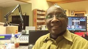 Un homme souriant dans un studio de radio