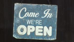 """Pancarte qui indique en anglais """"Entrez. Nous sommes ouvert""""."""