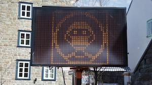 Un panneau électronique montre un visage masquée