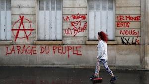 Des graffitis indiquant «la rage du peuple» et «le monde est à nous» sur des murs de Paris